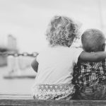 grayscale photography of two children sitting on ledge