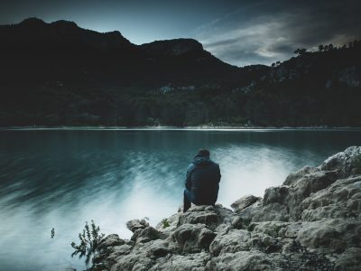 a man sits on a rock staring across a lake at dusk